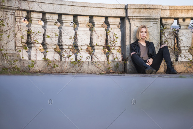 Caucasian woman sitting on ground leaning on wall