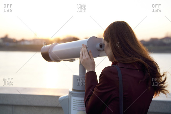Caucasian woman using binoculars at waterfront