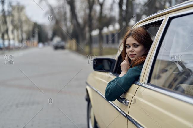 Caucasian woman driving car looking over shoulder
