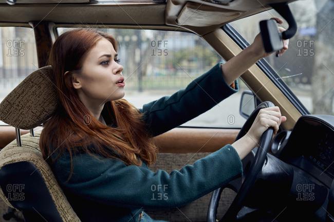 Caucasian woman driving car adjusting mirror