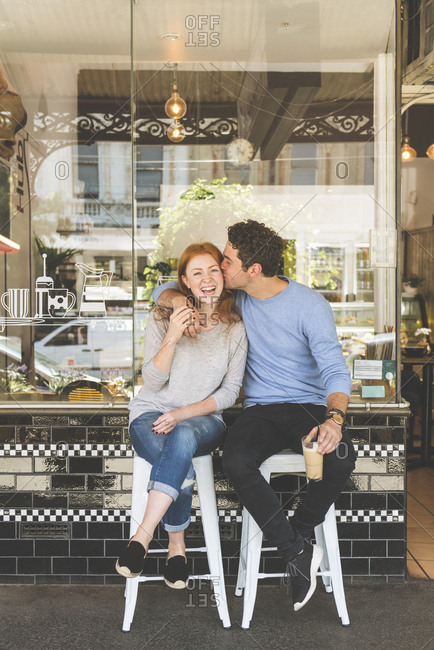 Smiling Caucasian couple sitting on stools outside coffee shop and kissing