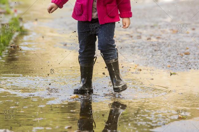 Caucasian girl wearing boots splashing in puddle