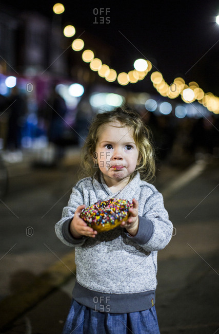 Caucasian girl eating donut outdoors at night