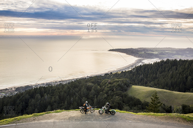 People on motorcycles at edge of cliff near ocean