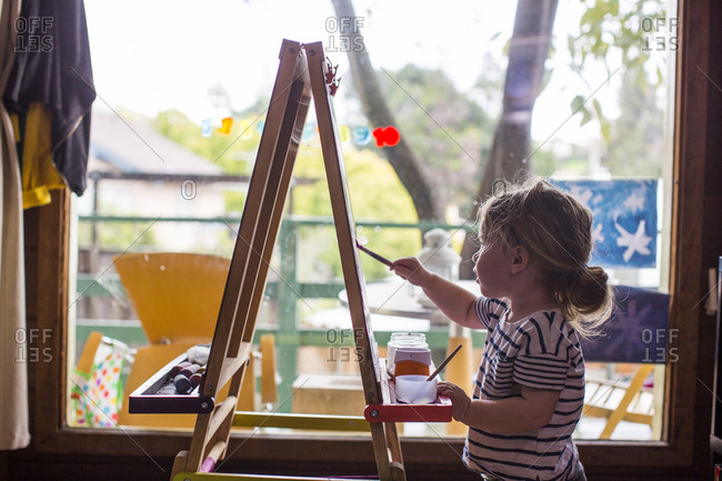 Caucasian girl painting on easel near window