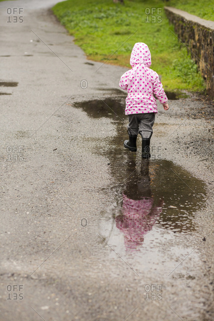 Caucasian girl wearing boots walking in puddle