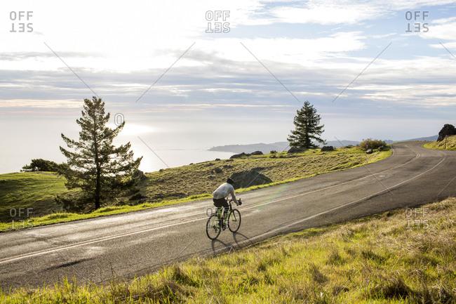 Caucasian man riding bicycle on road near ocean