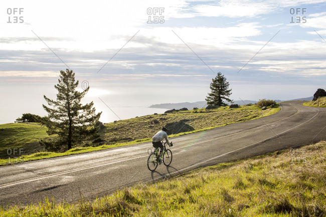 Caucasian man riding bicycle on road near ocean