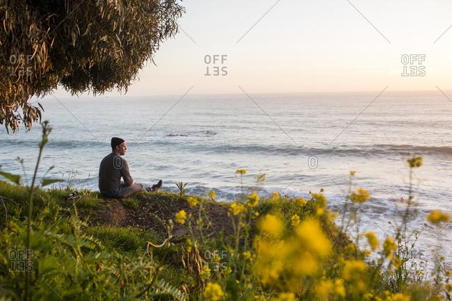 Caucasian man admiring scenic view of ocean at sunset