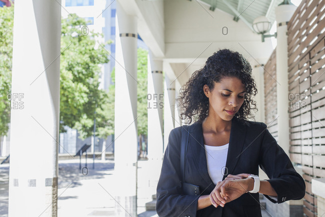Mixed Race businesswoman checking the time on wristwatch