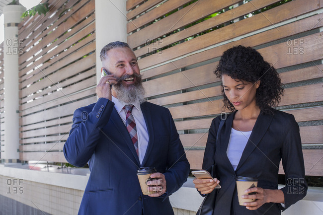 Business people standing outdoors using cell phones