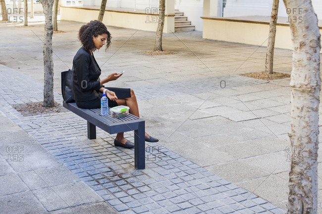Mixed Race businesswoman eating lunch on bench texting on cell phone