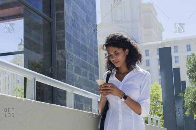 Mixed Race businesswoman texting on cell phone outdoors