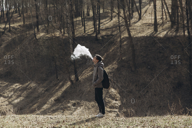 Middle Eastern man blowing vapor from mouth in forest