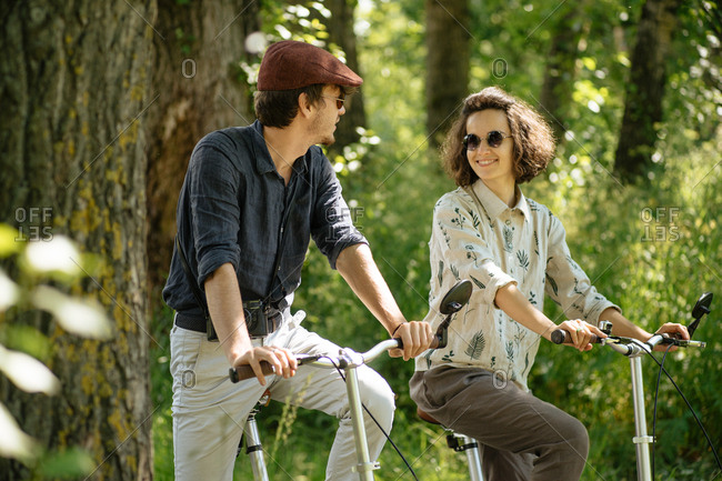 Hip couple riding bikes together in a wooded area