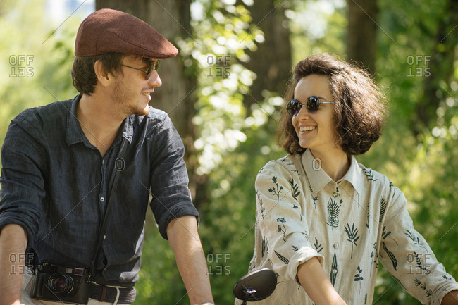 Hip couple standing together in a wooded area smiling
