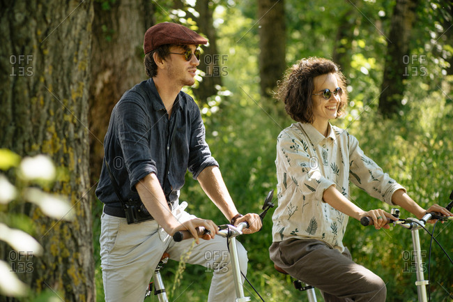 Hip couple riding bikes on a trail in the forest