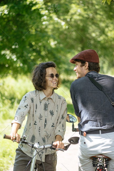 Hipster couple on bikes standing together talking in a forest