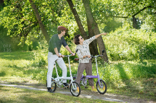 Hip young couple on bicycles in a park