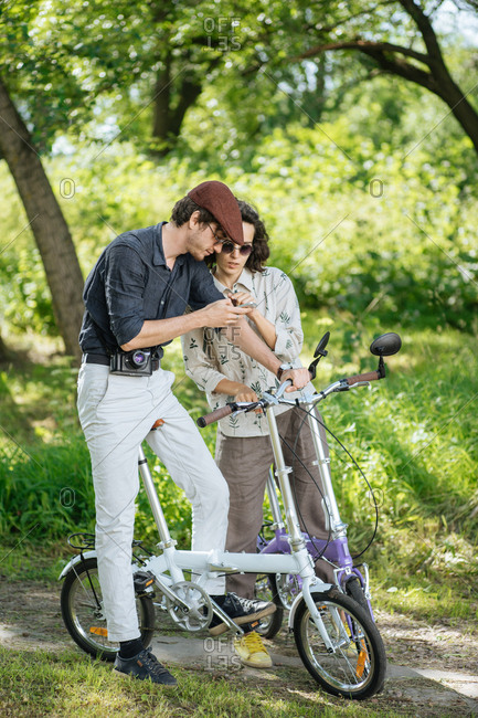 Hipster couple on bikes checking a phone together in a park
