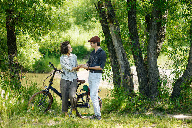 Hipster couple standing together beside a bike in a park