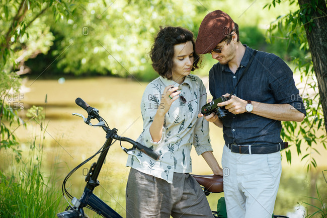Hip couple looking at a camera viewfinder together in a park