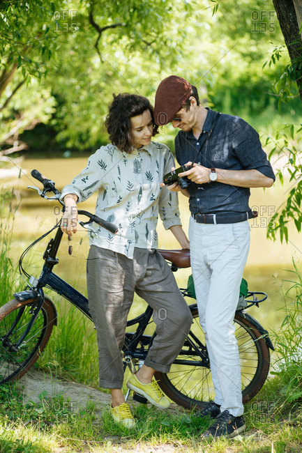 Young couple standing beside a bike looking at a camera in a park
