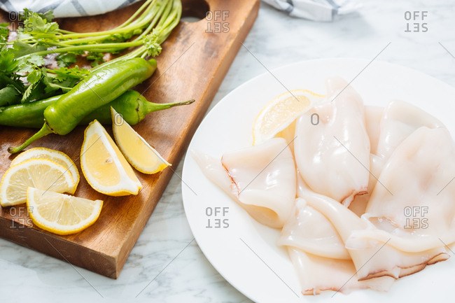 Raw ingredients for calamari on a plate and cutting board