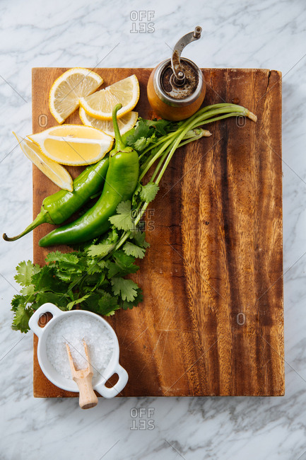 Cilantro, jalapeno peppers and lemon wedges on a wooden board