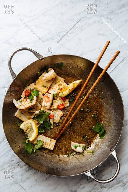 Squid in a pan with cilantro, peppers and chopsticks