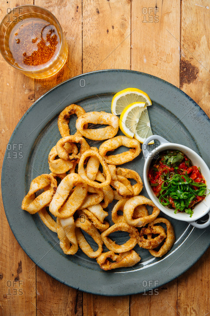 Platter of fried calamari with dipping sauce and a glass of beer