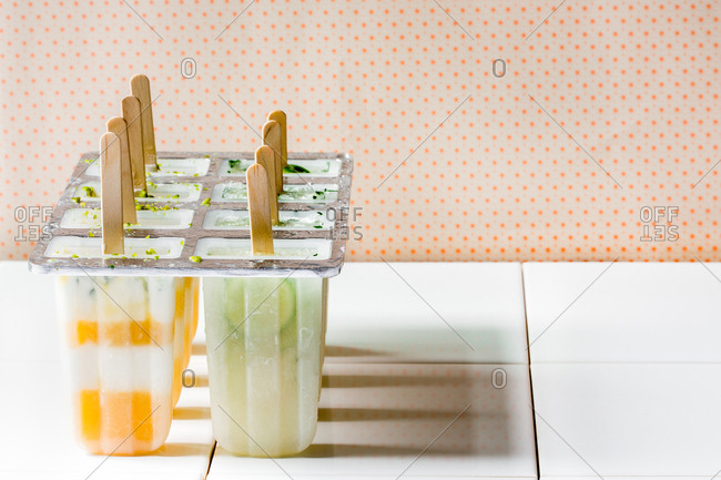 Mold with homemade frozen orange and lime popsicles