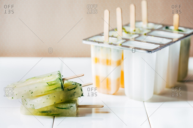 Homemade frozen lime popsicles and mold with orange pops