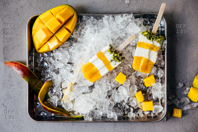 Mango ice pops on a metal tray with crushed ice