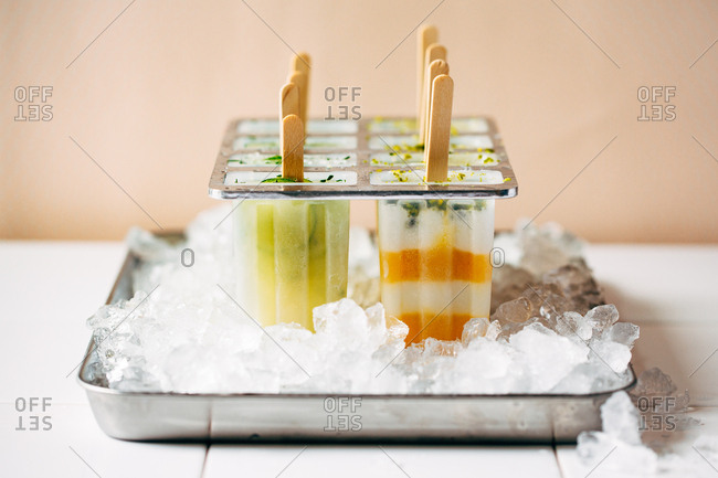 Orange and lime homemade frozen pops in a tray of ice