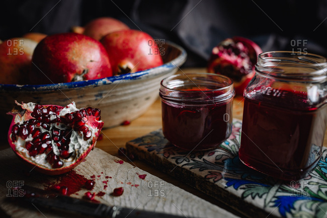 Jars of homemade pomegranate jelly and fresh open fruit
