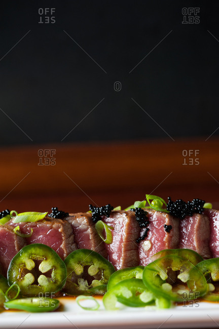 Beef Tataki slices arranged on a square plate with thin sliced jalapenos, green onions and black tobiko