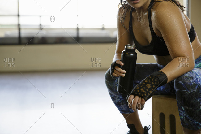 Midsection of sweaty female boxer holding bottle while resting in gym