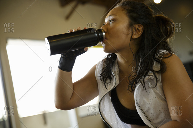 Female boxer drinking water after workout in gym