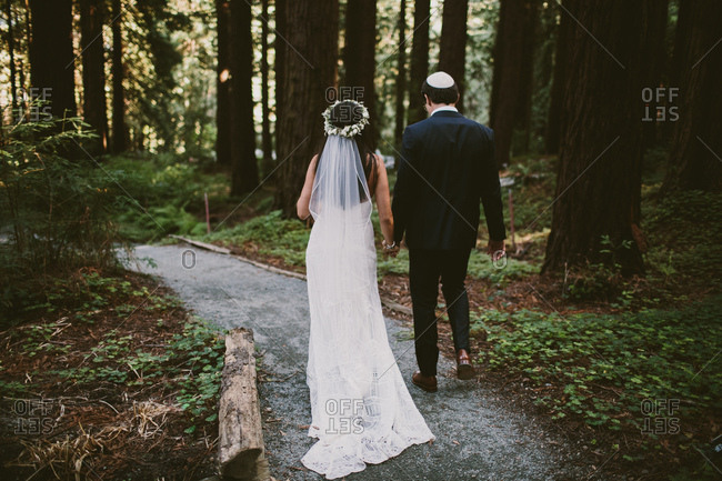 Bride and groom walking through redwoods