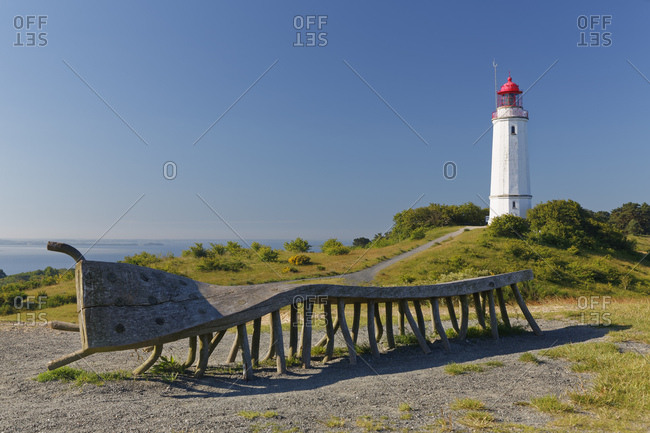 Germany- Mecklenburg-Western Pomerania- Hiddensee- Dornbusch lighthouse on the Schluckswiek- with old twisted wood bench in foreground