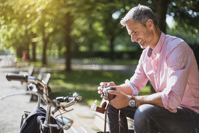Smiling man with bicycle looking at old-fashioned camera on a park bench