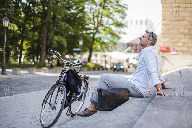 Relaxed man sitting on stairs in the city next to bicycle