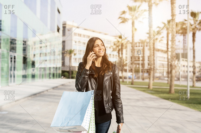 Portrait of smiling woman with shopping bags on the phone