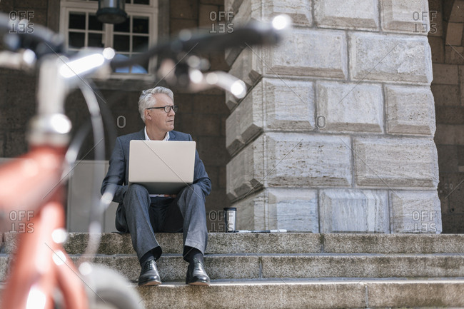 Senior businessman sitting on stairs outdoors working with laptop
