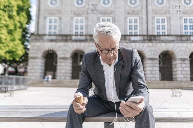 Senior businessman with ice cream cone sitting on bench looking at smartphone