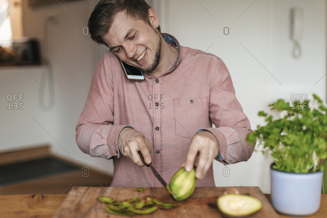 Smiling man on the phone chopping avocado in the kitchen