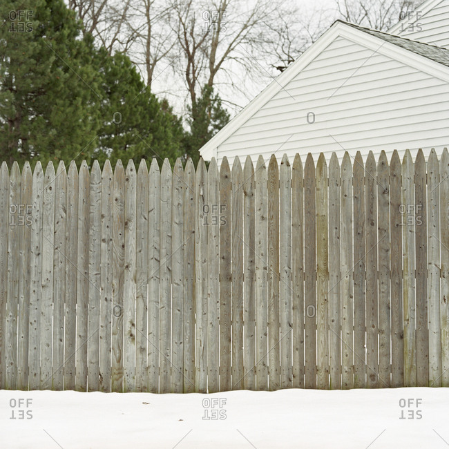Wooden fence in backyard with snow