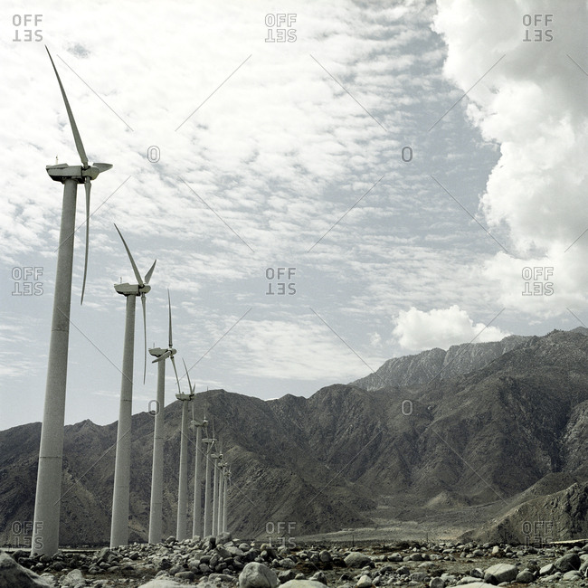 Row of wind turbines below mountain