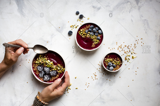Person holding a smoothie bowl topped with pistachios and frozen berries